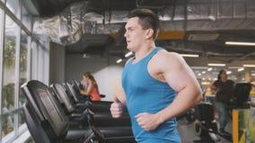 Stark man i idrottshallen - kroppsbyggarespring på det rinnande spåret i idrottshallen Royaltyfri Foto