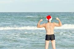 Stark man i jultomtenhattar med det nya året för inskrift på lodisarna Royaltyfria Foton