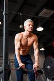 Stark man med den muskulösa kroppen som utarbetar i idrottshall Viktövning med skivstången i konditionklubba Arkivbild