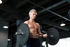 Stark man med den muskulösa kroppen som utarbetar i idrottshall Viktövning med skivstången i konditionklubba Arkivfoto