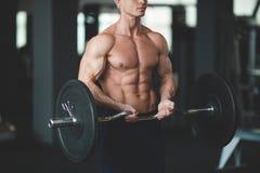 Stark man med den muskulösa kroppen som utarbetar i idrottshall Viktövning med skivstången i konditionklubba tonad bild Arkivfoto