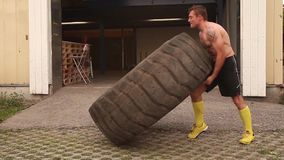 Stark man som bläddrar ett stort gummihjul stock video