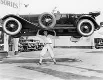 Stark man som lyfter en bil över hans huvud (alla visade personer inte är längre uppehälle, och inget gods finns Leverantörgarant Arkivfoto