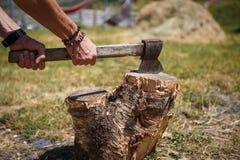 Stark mans hand med en yxa som hugger av tr? p? campa i en bergig region av Georgia royaltyfria foton