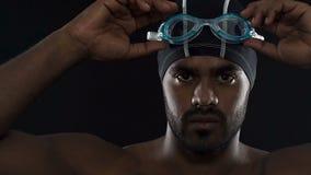 Stark motiverad simmare som sätter på skyddsglasögon som får klar för konkurrens lager videofilmer