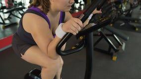 Stark motivierte pralle Frau, die schnell am Standrad, Sportclub reitet stock footage