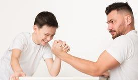 Stark pojke som försöker att segra och att konkurrera med farsan i armbrottning arkivfoton