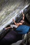 Stark pojke som klättrar en sten royaltyfria bilder