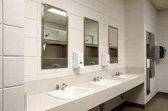 Stark public bathroom. Perspective shot of a countertop with three sinks and mirors in a stark public school bathroom Royalty Free Stock Image