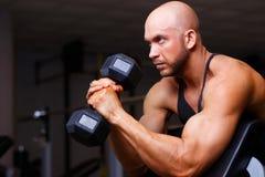 Stark riven sönder skallig man med enorma muskler som pumpar järn Sportmor royaltyfri bild