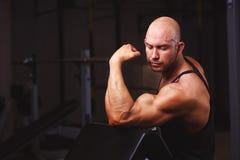 Stark riven sönder skallig man som visar stora muskler i idrottshall Sport, royaltyfri foto