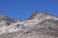 Stark rocky peaks against blue sky Stock Photos