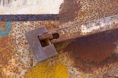 Stark rostig hänglås med den tunga järnstången som låser metalldörren Arkivfoton