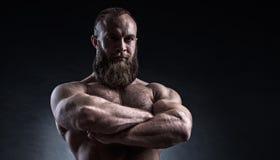 Stark skäggig man med perfekt abs, skuldror, biceps, triceps Arkivfoto