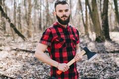 Stark skogsarbetare som hugger av trä Royaltyfria Bilder