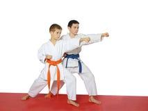 Stark stansmaskinhand i kapaciteten av idrottsman nen med ett blått bälte och det orange bältet Royaltyfri Foto