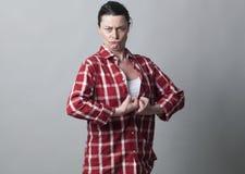Stark 40-talkvinna med åtsittande nävar tillsammans klibba ut bröstkorgen Arkivbilder
