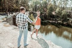 Stark understöd maninnehavhand av hans stråla flickvän som kommer närmare sjön arkivbilder
