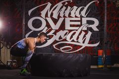 Stark ung idrottsman som försöker att lyfta ett enormt tungt rubber hjul royaltyfri fotografi
