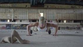 Stark ung kvinna i militär likformig som vrider om sig från golvet på ett konkret golv i en övergiven byggnad arkivfilmer