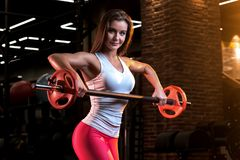 Stark ung kvinna med den härliga idrotts- kroppen som gör övningar med skivstången fotografering för bildbyråer