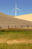 Stark White Power Generating Windmill. Power generating wind turbine on cultivated, fresh ploughede and wheat covered hills, Rio Vista California stock images