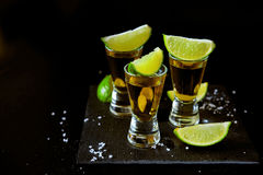 Starka alkoholdrinkar Tequilaskott med salta och limefruktskivor Arkivbilder