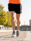 Starka ben av ung löparespring som joggar i stadsgata på solnedgången i stadsutbildningsgenomkörare arkivbild