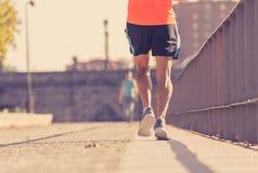 Starka ben av ung löparespring som joggar i stadsgata på solnedgången i stadsutbildningsgenomkörare royaltyfri bild