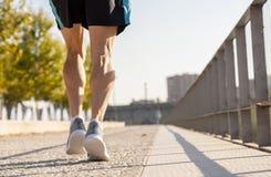 Starka ben av ung löparespring som joggar i stadsgata på solnedgången i stadsutbildningsgenomkörare arkivfoton
