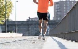 Starka ben av ung löparespring som joggar i stadsgata på solnedgången i stadsutbildningsgenomkörare arkivbilder