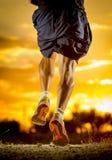 Starka ben för ung man av slingaspring på den fantastiska sommarsolnedgången i sport och sund livsstil arkivfoto