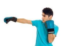 Starka brunettsportar man oracticing boxning i blåa handskar som isoleras på vit bakgrund Arkivfoto
