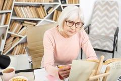 Starke ältere Frauenleseaufgabe lizenzfreie stockfotos