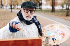 Starke ältere männliche Person, die modernes Bild schafft stockbilder