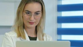 Starke Ärztin in der Glasfunktion auf Laptop am Aufnahmeschreibtisch Stockfoto