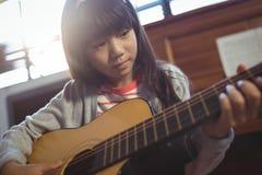Starke übende Gitarre des Mädchens Lizenzfreie Stockfotografie