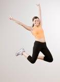 Starke athletische Frau, die aufgeregt in mitten in der Luft springt Stockfotos