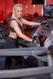 Starke athletische Frau, die in einer Turnhalle ausarbeitet Lizenzfreies Stockfoto