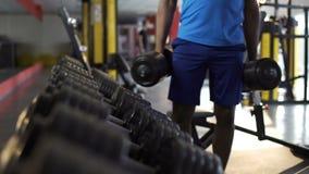 Starke athletische Männer, die schwere Dummköpfe für aktives Training in der Turnhalle, Eignung nehmen stock footage
