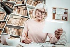 Starke blonde ältere weibliche Person, die Anmerkungen macht lizenzfreie stockfotografie
