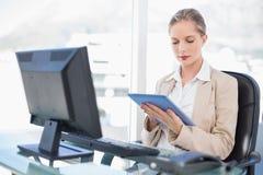 Starke blonde Geschäftsfrau, die Tablette verwendet Lizenzfreie Stockfotografie