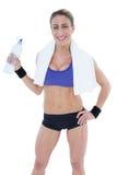 Starke blonde haltene Wasserflasche, die an der Kamera lächelt Lizenzfreie Stockbilder