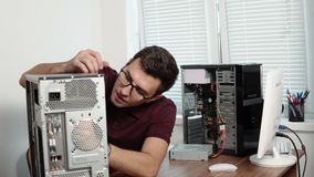 Starke Computerservice-Arbeitskraft in den Gläsern, die einen defekten Computer im Büro reparieren und Computerhardware verbesser stock video