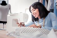 Starke Damenschneiderin, die mit Nähmaschine arbeitet lizenzfreie stockfotografie