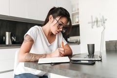 Starke ernste junge Frau, die Laptop-Computer Schreibensanmerkungen verwendet Lizenzfreies Stockbild
