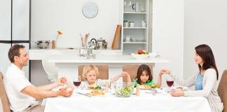 Starke Familie, die vorher zu Mittag essen betet Lizenzfreie Stockbilder