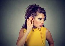 Starke Frau, die auf schockierende Gerüchte hört stockfotografie