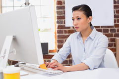 Starke Frau, die Computer am Schreibtisch verwendet Lizenzfreie Stockfotografie