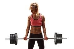 Starke Frau, die ein Schwergewicht anhebt Stockbild